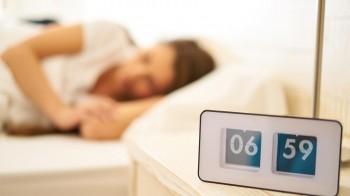 vintage flip clock with sleeping woman before wakeup call